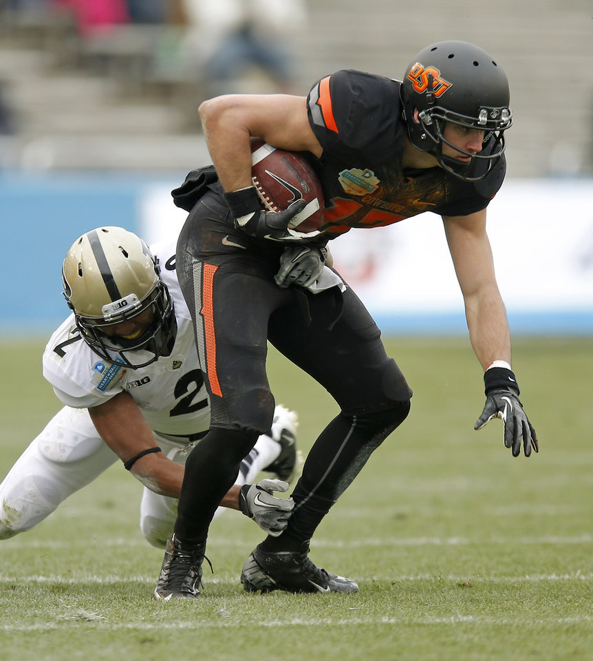 Photo - Oklahoma State's Charlie Moore (17) tries to get past Purdue's Frankie Williams (2) during the Heart of Dallas Bowl football game between Oklahoma State University and Purdue University at the Cotton Bowl in Dallas, Tuesday, Jan. 1, 2013. Oklahoma State won 58-14. Photo by Bryan Terry, The Oklahoman