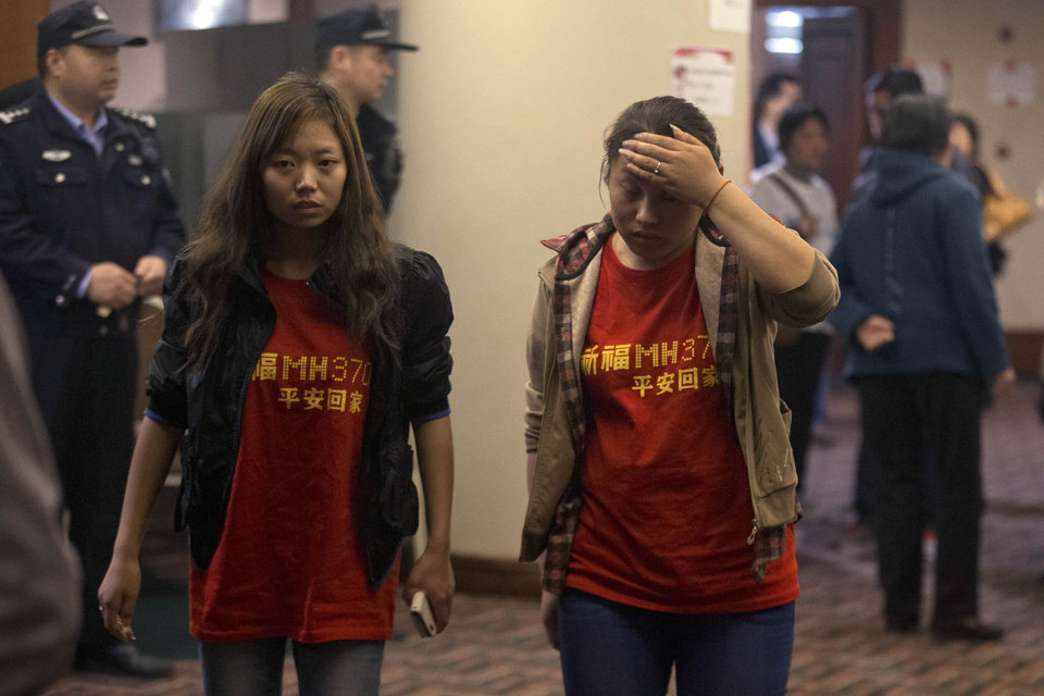 Photo - Relatives of the Chinese passengers onboard the Malaysia Airlines flight MH370 wear T-shirts with the words