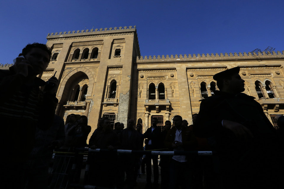 Photo - Egyptian policemen stand guard in front of the Museum of Islamic Art at the site of a blast at the Egyptian police headquarters in downtown Cairo, Egypt, Friday, Jan. 24, 2014.  Egypt's antiquities minister says the car bombing that struck the main police headquarters in Cairo earlier in the day has caused major damage to the nearby Islamic art museum.(AP Photo/Amr Nabil)