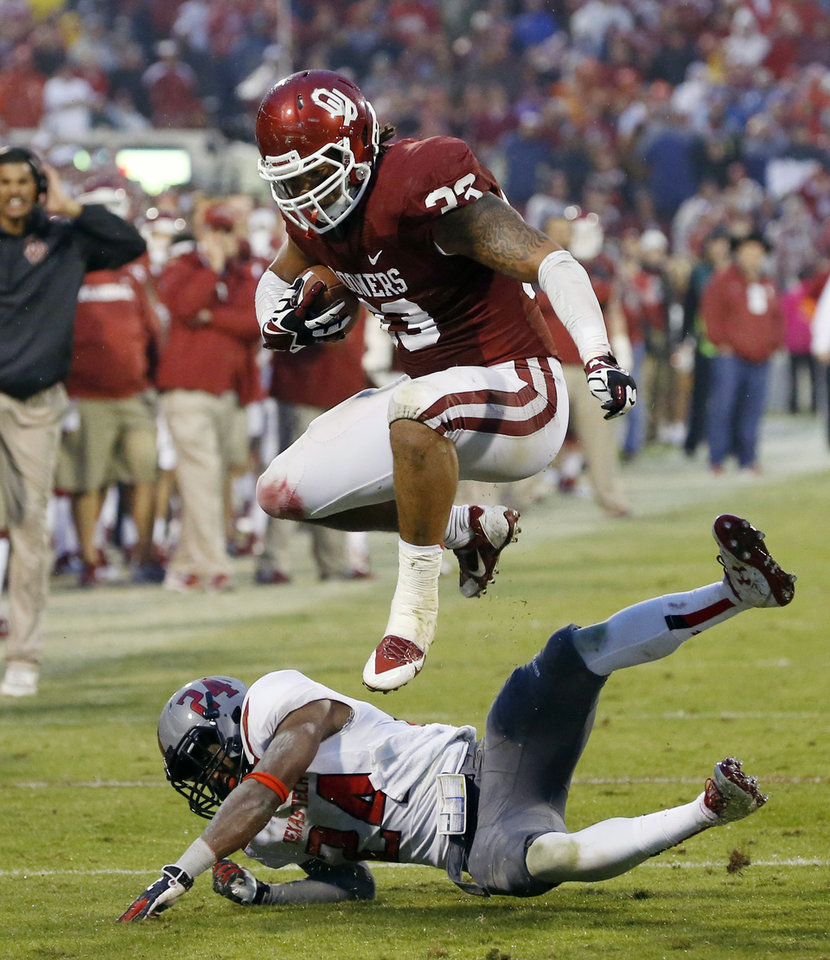 Oklahoma fullback Trey Millard (33) jumps over Texas Tech defensive back Bruce Jones (24) in the fourth quarter of an NCAA college football game in Norman, Okla., Saturday, Oct. 26, 2013. Oklahoma won 38-30. (AP Photo/Sue Ogrocki)