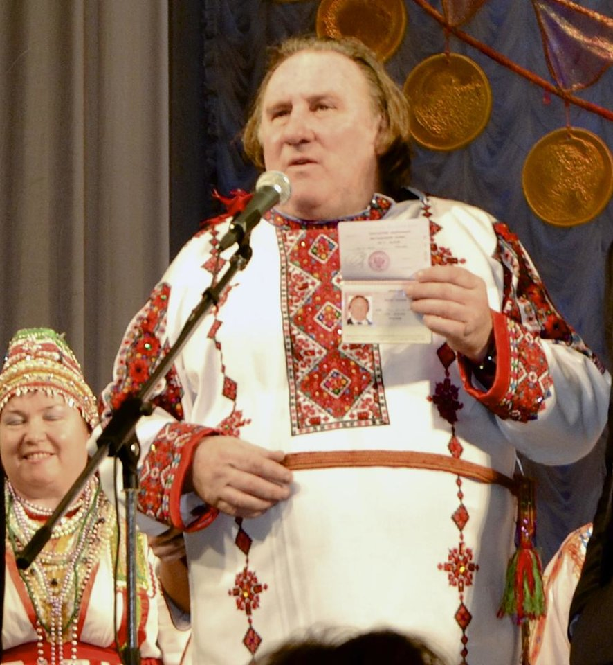 Photo - CORRECTING DATE TO SUNDAY JAN. 6  - French actor Gerard Depardieu poses with his new Russian passport on a theatre stage, wearing a traditional folk outfit, after he arrived in the city of Saransk, some 700 km (435 miles) east of Moscow, Russia, on Sunday, Jan. 6, 2013.  Depardieu has received a Russian passport after flying to Russia for a late night dinner with Putin. Depardieu sought Russian citizenship as part of his battle against a proposed super tax on millionaires in France, and Putin granted his request last week. (AP Photo/Mordovmedia.ru)