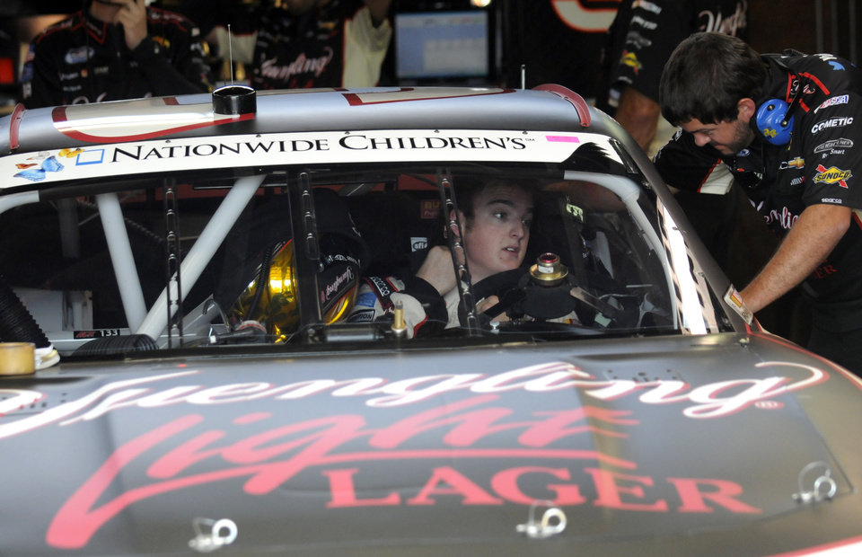 Photo - Ty Dillon talks to a crew member in the garage during practice for the NASCAR Nationwide Series Nationwide Children's Hospital 200 auto race at Mid-Ohio Sports Car Course Friday, Aug. 15, 2014 in Lexington, Ohio. (AP Photo/Tom E. Puskar)