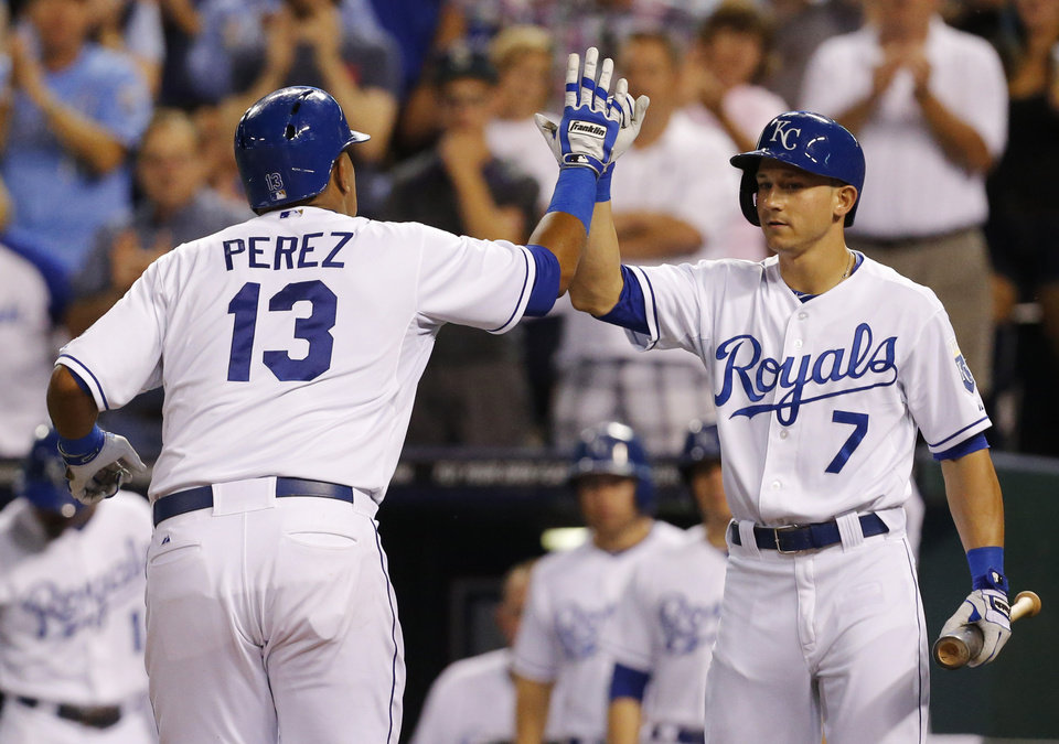 Kansas City Royals' Salvador Perez (13) is congratulated by teammate David Lough (7) after hitting a solo home run off Seattle Mariners starting pitcher Erasmo Ramirez in the fourth inning of a baseball game at Kauffman Stadium in Kansas City, Mo., Tuesday, Sept. 3, 2013. (AP Photo/Orlin Wagner)