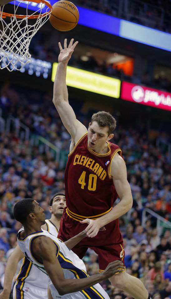 Photo - Cleveland Cavalier's Tyler Zeller, right, throws the ball up for a shot as he draws a blocking foul by Utah Jazz's  Jeremy Evans during an NBA basketball game in Salt Lake City, Friday, Jan. 10, 2014. (AP Photo/George Frey)