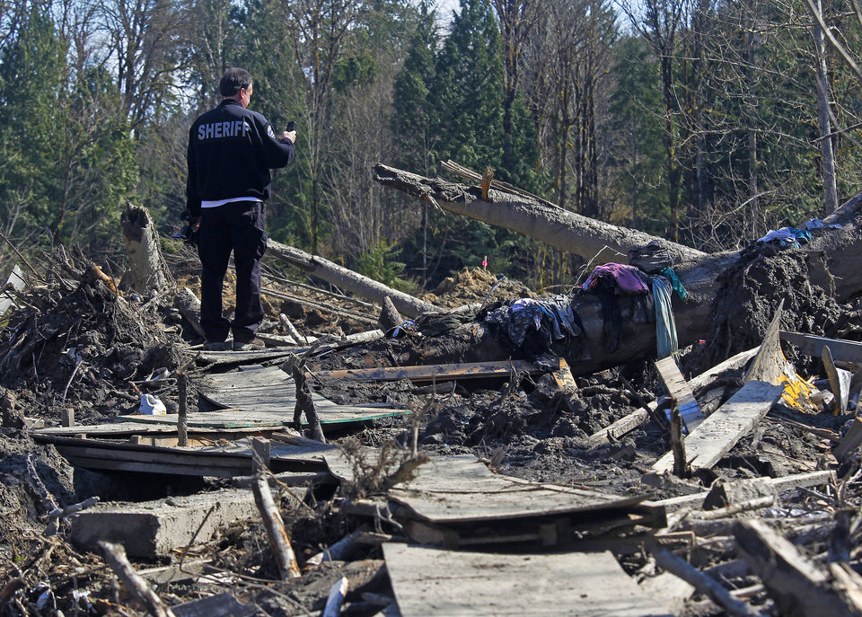 Photo - A sheriff official takes photos of debris from a massive fatal mudslide near Oso, Wash., on Tuesday, April 1, 2014. The March 22 mudslide destroyed a  rural mountainside community northeast of Seattle. (AP Photo/The Herald, Mark Mulligan) MANDATORY CREDIT.