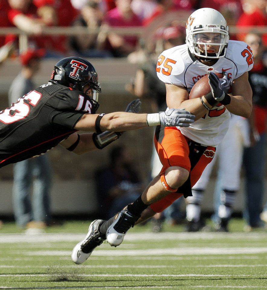 Photo - OSU's Josh Cooper (25) tries to get past Cody Davis (16) of Texas Tech in the second quarter during the college football game between the Oklahoma State University Cowboys and Texas Tech University Red Raiders at Jones AT&T Stadium in Lubbock, Texas, Saturday, October 16, 2010. Photo by Nate Billings, The Oklahoman