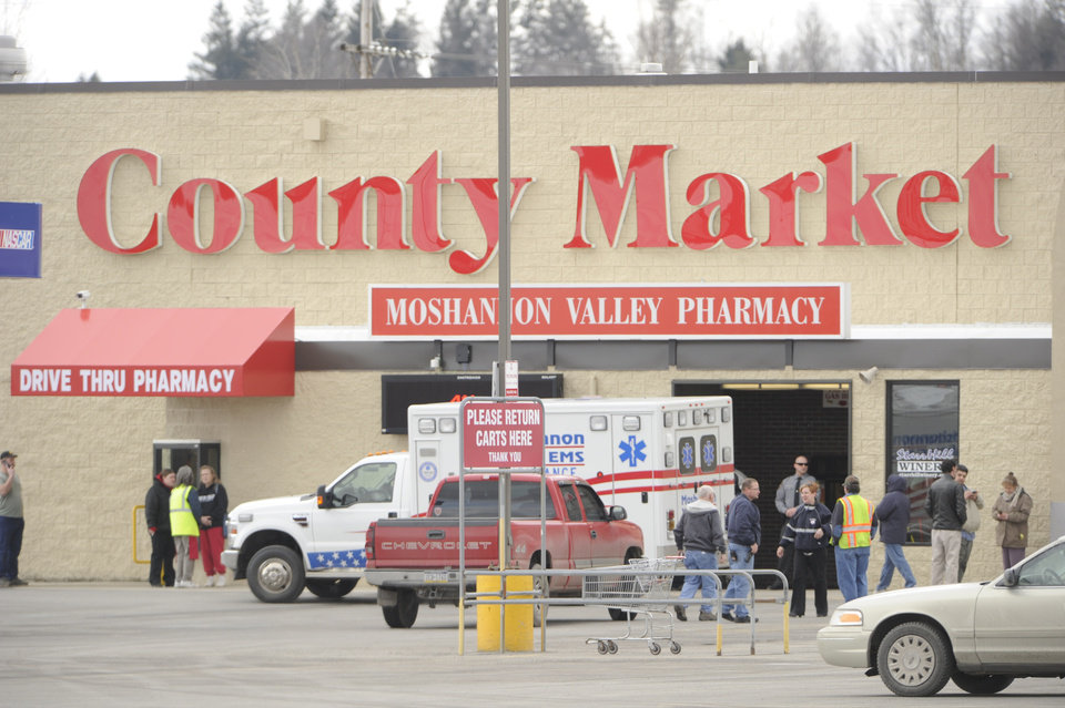 State police work the scene of a shooting Thursday, March 28, 2013, at the County Market grocery store on the outskirts of Philipsburg, Pa. Pennsylvania State Police say the gunman in a supermarket shooting is a retired state trooper, and the woman he shot before killing himself had been his wife. State police spokeswoman Maria Finn said Thursday troopers were working to notify their closest victims, holding up public identification of the two. (AP Photo/Centre Daily Times, Nabil K Mark) MANDATORY CREDIT; MAGS OUT