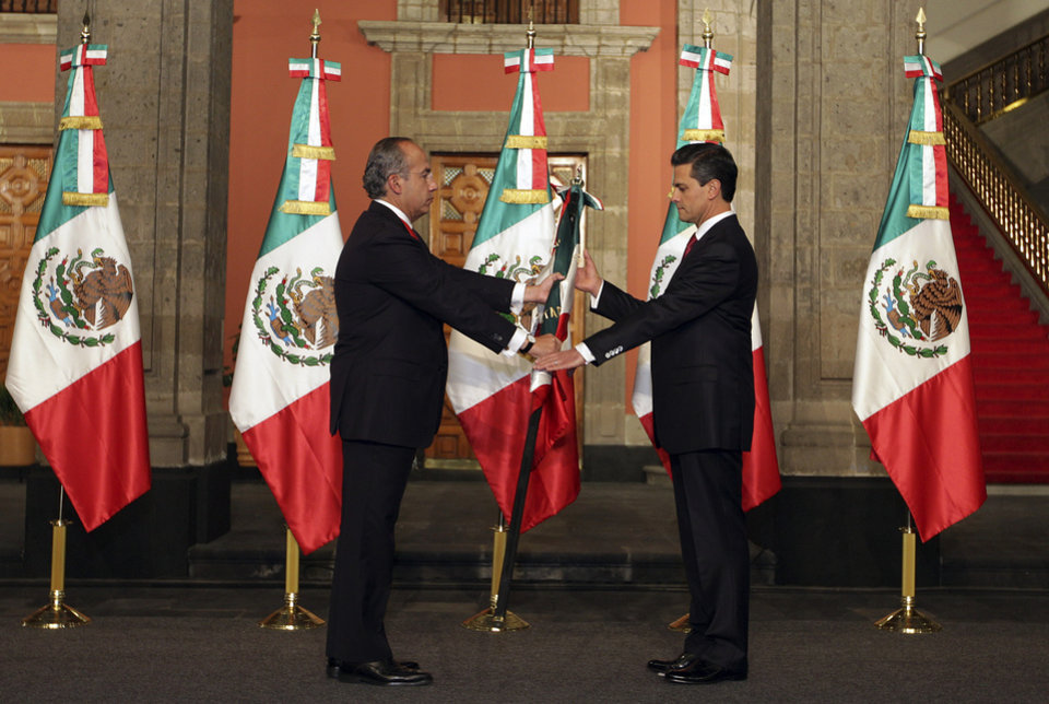 In this image released by the press office of president-elect Enrique Pena Nieto on Saturday Dec. 1, 2012, Mexico's outgoing president, Felipe Calderon, left, gives a Mexican flag to president-elect Enrique Pena Nieto during the official transfer of command ceremony at the National Palace in Mexico City, Saturday Dec. 1, 2012. Pena Nieto will be officially sworn in as Mexico's new President during a ceremony at the National Congress later on Saturday. (AP Photo/Press Office of president-elect Enrique Pena Nieto)