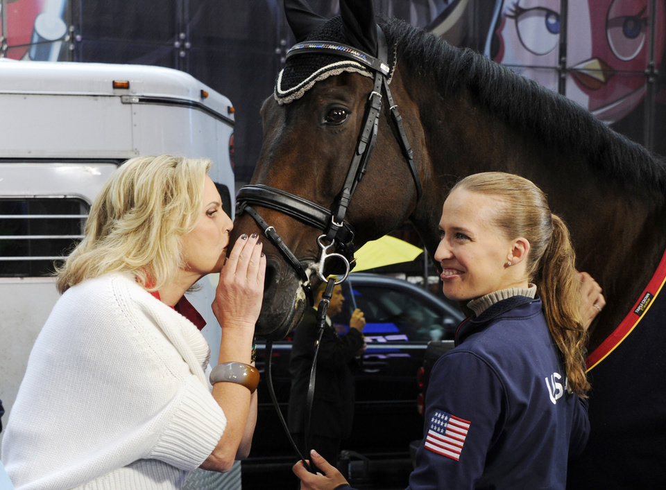 This photo released by Good Morning America, Wednesday, Oct. 10, 2012, shows Ann Romney, wife of Republican presidential nominee Mitt Romney, left, planting a kiss on Lord Ludger while his rider Rebecca Hart watches on the set of the television show in New York. Romney said Wednesday that her love of horses helped her overcome her fear that multiple sclerosis would put her in a wheelchair. She was guest hosting ABC\'s