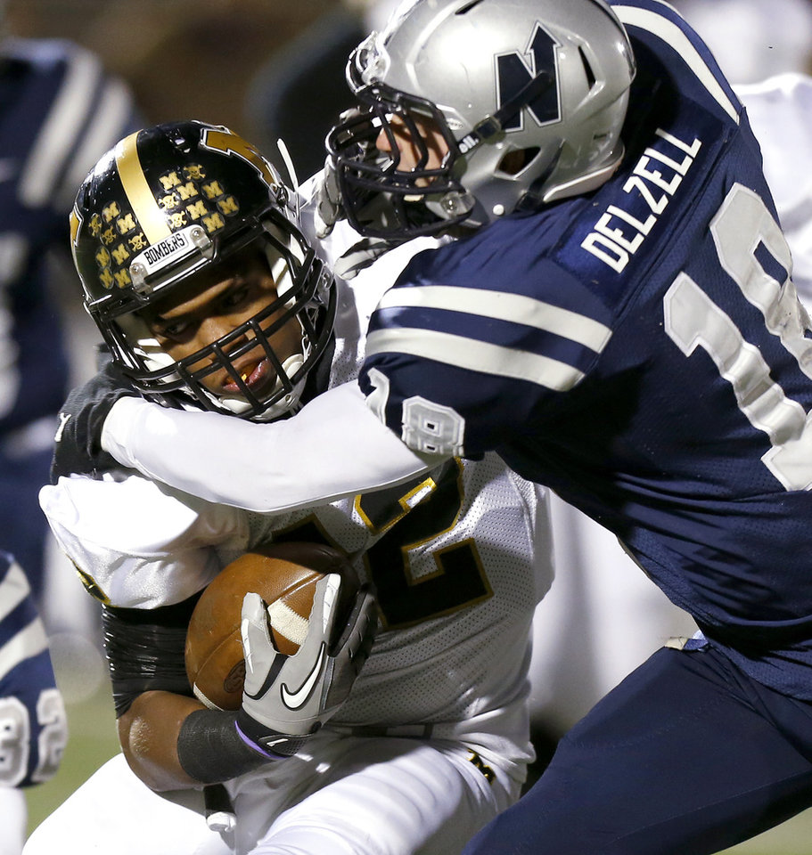 Photo - Edmond North's Sam Delzell tries to bring down Midwest City's Cornell Neal during their high school football game at Wantland Stadium in Edmond, Thursday, October 25, 2012. Photo by Bryan Terry, The Oklahoman