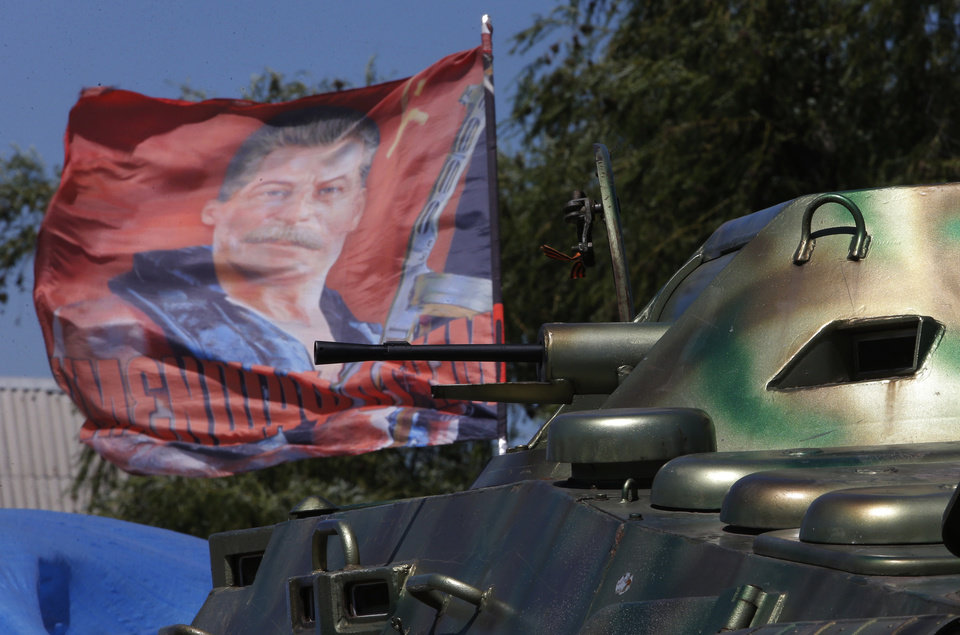 Photo - A flag with a portrait of Soviet dictator Josef Stalin is installed near an APC at a pro-Russian fighters' checkpoint at the village of Karlivka near Donetsk, eastern Ukraine Tuesday, July 1, 2014. Ukraine renewed its attacks against armed pro-Russia separatists Tuesday after the president called off a unilateral cease-fire, carrying out air and artillery strikes against rebel positions in eastern Ukraine. (AP Photo/Dmitry Lovetsky)