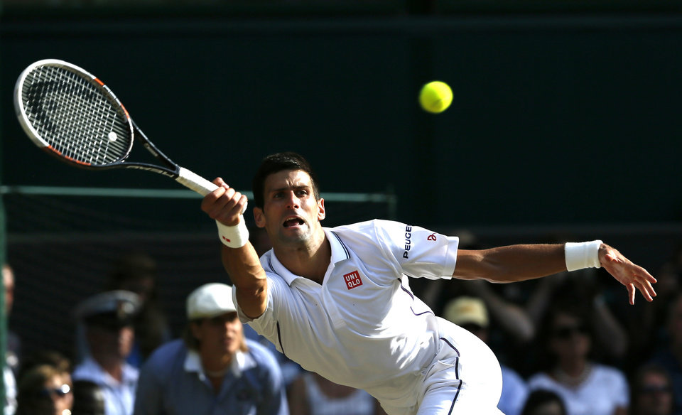 Photo - Novak Djokovic of Serbia plays a return to Roger Federer of Switzerland during their men's singles final at the All England Lawn Tennis Championships in Wimbledon, London, Sunday, July 6, 2014. (AP Photo/Ben Curtis)