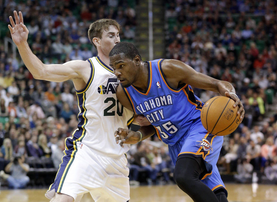Photo - Oklahoma City Thunder's Kevin Durant (35) drives around Utah Jazz's Gordon Hayward in the first quarter of an NBA basketball game Wednesday, Oct. 30, 2013, in Salt Lake City. (AP Photo/Rick Bowmer)