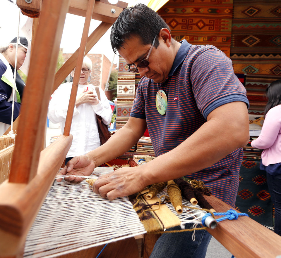 Photo -  Mel Mendez weaves on a loom at his booth during the Festival of the Arts. [PHOTO BY STEVE SISNEY, THE OKLAHOMAN]