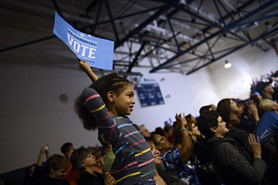 Alicya Feliciano, 5, holds up a sign as former President Bill Clinton speaks at Indian River High School in Chesapeake, Va. on Saturday, Nov. 3, 2012. (AP Photo/The Virginian-Pilot, Amanda Lucier) MAGS OUT