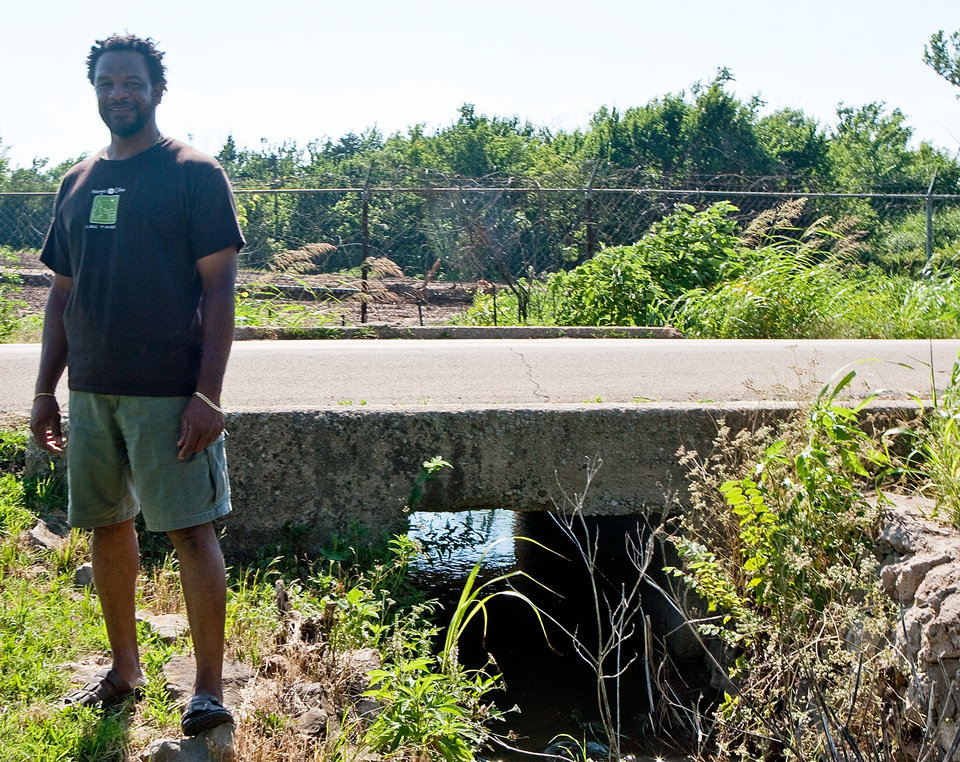 Melvin Morris Jr. stands beside the creek that he played in as a kid, which was run off water from a superfund site. Clean up is taking place on the superfund site in Cushing, Okla onTuesday June 22, 2009. Photo by Mitchell Alcala, The Oklahoman ORG XMIT: KOD