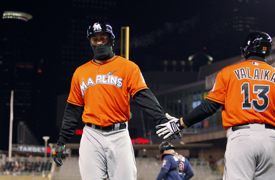 Photo - Miami Marlins' Giancarlo Stanton, left, is congratulated by Chris Valaika (13) after scoring on Rob Brantly's RBI double against Minnesota Twins starting pitcher Mike Pelfrey during the fifth inning in the second baseball game of a doubleheader Tuesday, April 23, 2013, in Minneapolis. (AP Photo/Genevieve Ross)
