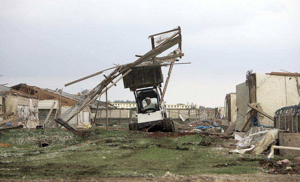A worker clears debris at Farm 62 of Seaboard Foods near Lacey, Okla., Saturday, May 24, 2008. The farm was severely damaged by a tornado. BY SARAH PHIPPS, THE OKLAHOMAN