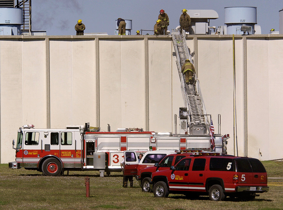 Photo - In 2001, Oklahoma City firefighters cleaned up after a fire at the Dayton Tire Plant, 2500 S Council. - PHOTO BY NATE BILLINGS, THE OKLAHOMAN