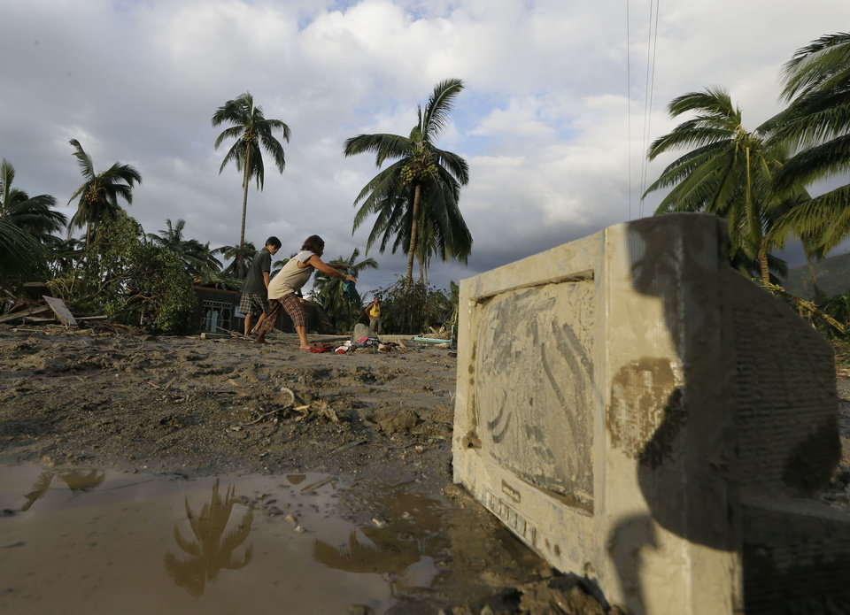 Residents retrieve belongings at the flash flood-hit village of Andap, New Bataan township, Compostela Valley in southern Philippines Wednesday Dec. 5, 2012. Typhoon Bopha, one of the strongest typhoons to hit the Philippines this year, barreled across the country\'s south on Tuesday, killing scores of people while triggering landslides, flooding and cutting off power in two entire provinces. (AP Photo/Bullit Marquez)