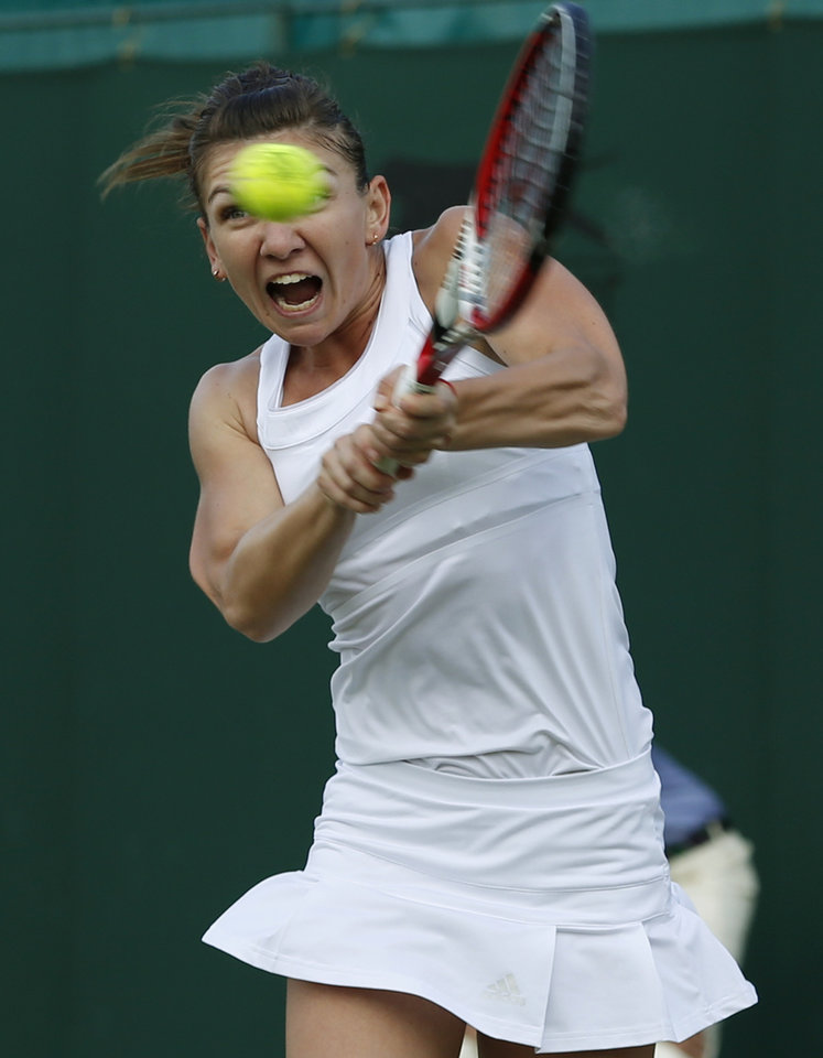 Photo - Simona Halep of Romania plays a return to Belinda Bencic of Switzerland during their women's singles match at the All England Lawn Tennis Championships in Wimbledon, London, Saturday, June 28, 2014. (AP Photo/Alastair Grant)