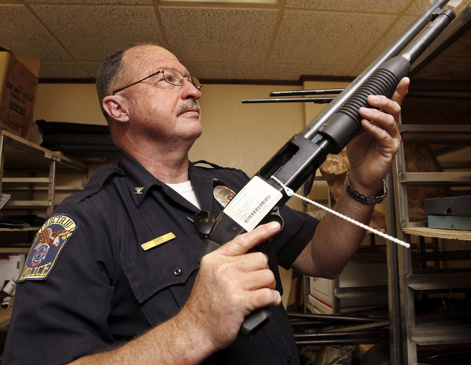 Choctaw Police Chief Conny Clay shows off one of several shotguns gathering dust in the department's property room on Thursday, July 26, 2012.  Photo by Jim Beckel, The Oklahoman. <strong>Jim Beckel - THE OKLAHOMAN</strong>