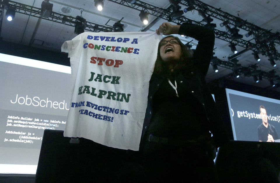 Photo - Claudia Tirado protests while Dave Burke, director of engineering at Android, speaks during the Google I/O 2014 keynote presentation in San Francisco, Wednesday, June 25, 2014. Tirado was escorted from the room by security. (AP Photo/Jeff Chiu)