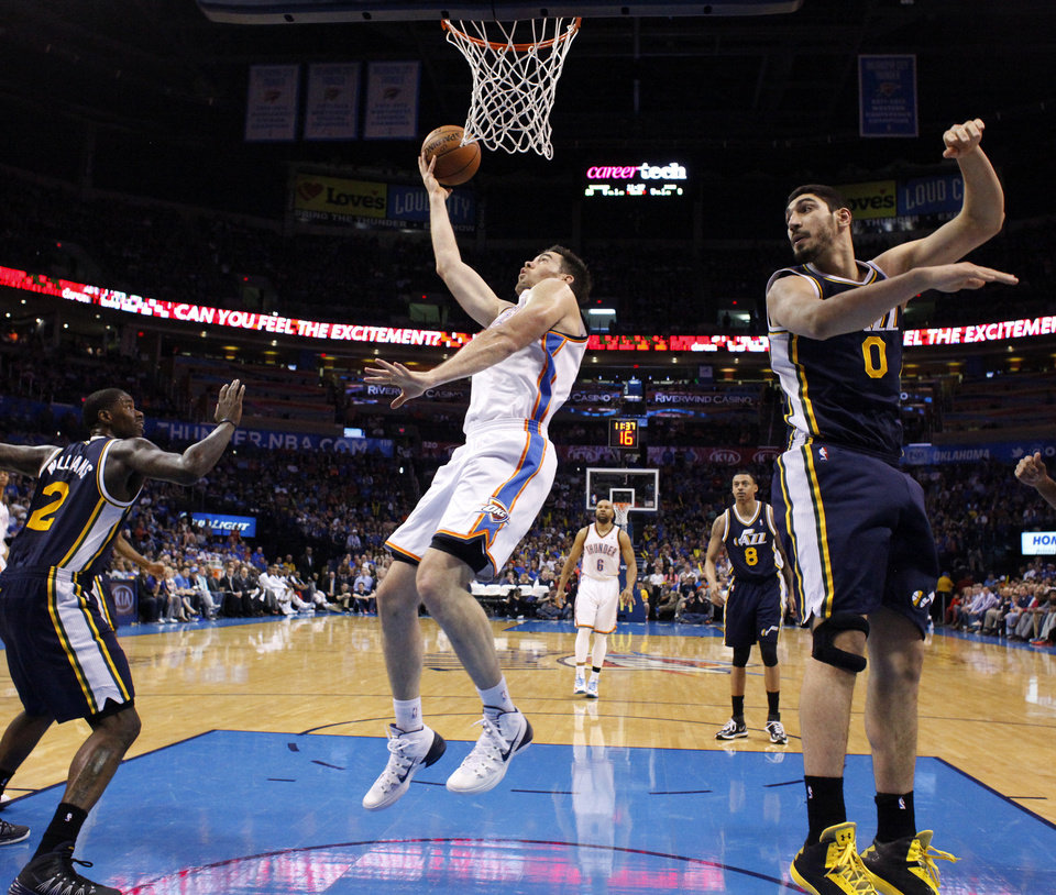 Oklahoma City 's Nick Collison (4) shoots a lay up in between Utah's Marvin Williams (2) and Enes Kanter (0) during the NBA game between the Oklahoma City Thunder and the Utah Jazz at the Chesapeake Energy Arena, Sunday, March 30, 2014, in Oklahoma City. Photo by Sarah Phipps, The Oklahoman
