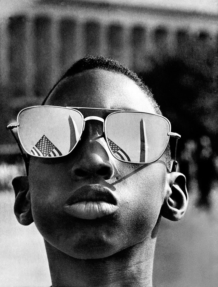 FILE - In this Aug. 28, 1963 file photo, the top of the Washington Monument and part of a U.S. flag are reflected in the sunglasses of Austin Clinton Brown, 9, of Gainesville, Ga., as he poses at the Capitol where he joins others in the March on Washington. (AP Photo/File)