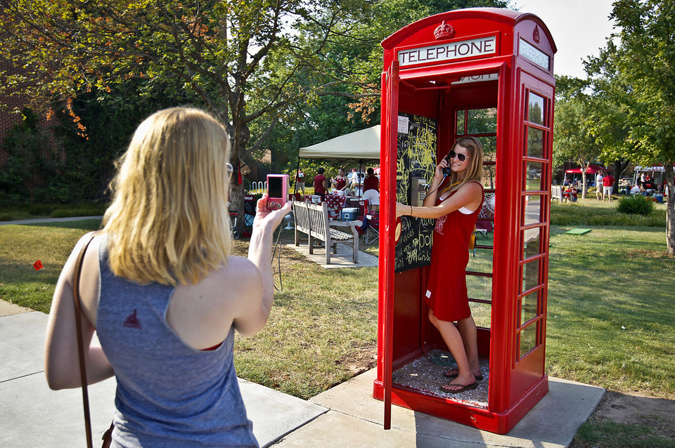Photo - Lauren Landerfeld takes a photo of her friend Lisa Ptak as they pose for photos in a phone boot before the start of the college football game between the University of Oklahoma Sooners (OU) and the Tulsa University Hurricanes (TU) at the Gaylord Family-Memorial Stadium on Saturday, Sept. 3, 2011, in Norman, Okla. 