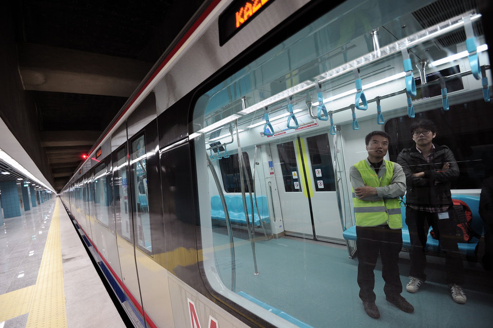 Photo - Two Japanese tecnicians wait inside a train for the inauguration of the tunnel called the  Marmaray in Istanbul, Turkey, Tuesday, Oct. 29, 2013. Turkey is for the first time connecting its European and Asian sides with a railway tunnel set to open Tuesday, completing a plan initially proposed by an Ottoman sultan about 150 years ago. The Marmaray, is among a number of large infrastructure projects under the government of Prime Minister Recep Tayyip Erdogan that have helped boost the economy but also have provoked a backlash of public protest.(AP Photo)