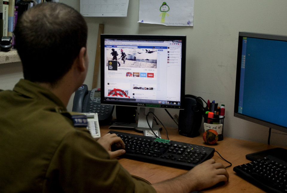 An Israeli soldier looks at the Facebook page of the IDF, at the IDF spokesperson office in Jerusalem, Thursday, Nov. 15, 2012. The hostilities between Israel and Hamas have found a new battleground: social media. The Israeli Defense Force and Hamas militants have exchanged fiery tweets throughout the fighting in a separate war to influence public opinion. (AP Photo/Sebastian Scheiner)