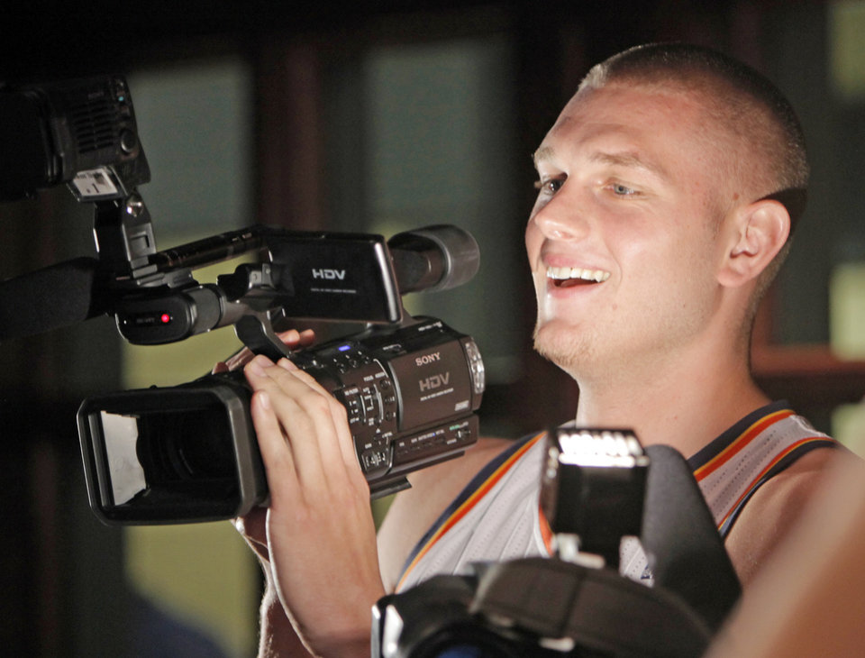 Photo - Cole Aldrich asks a question of teammate Jeff Green (not pictured) after borrowing a video camera from a member of the media during media day for the Oklahoma City Thunder at the Ford Center in downtown Oklahoma City, Monday, Sept. 27, 2010. Photo by Nate Billings, The Oklahoman