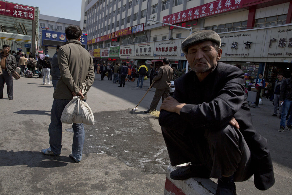 "Photo - A man squats on a concrete barrier as others wash and scrub the site of the Wednesday explosion outside the Urumqi South Railway Station in Urumqi in northwest China's Xinjiang Uygur Autonomous Region on Thursday, May 1, 2014.  Chinese President Xi Jinping demanded ""decisive"" action against terrorism after a slashing and bomb attack at a Xinjiang train station killed three people and injured 79 while the leader was wrapping up a tour of the far-western region.(AP Photo/Ng Han Guan)"