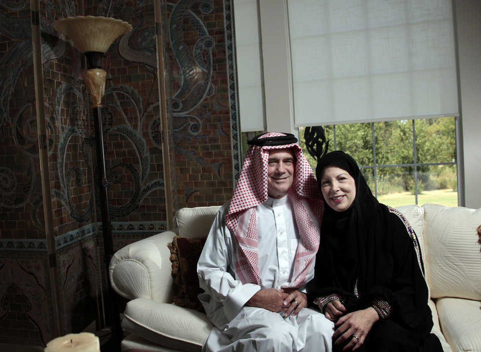 Photo - David and Carol Hartmann pose for a pictured in outfits they wore in Saudi Arabia at their home in Edmond, Okla., Thursday, July 19, 2012. Photo by Sarah Phipps, The Oklahoman. ORG XMIT: OKOKL