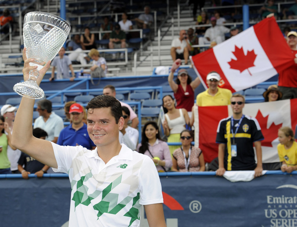 Photo - Milos Raonic, of Canada, poses with the trophy after he beat compatriot Vasek Pospisil in the men's singles final at the Citi Open tennis tournament, Sunday, Aug. 3, 2014, in Washington. Raonic won 6-1, 6-4. (AP Photo/Nick Wass)