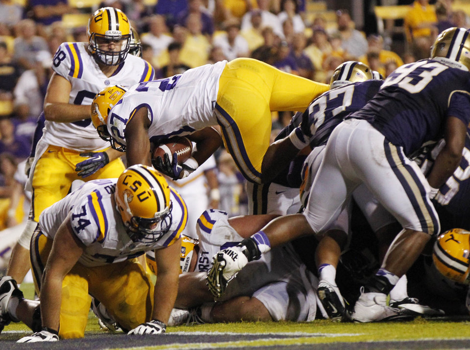Photo -   LSU running back Kenny Hilliard (27) dive into the end zone for a touchdown during the second half of an NCAA college football game against Washington in Baton Rouge, La., Saturday, Sept. 8, 2012. (AP Photo/Gerald Herbert)