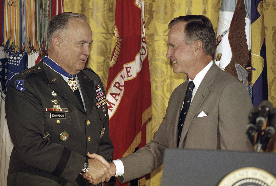 Photo - FILE - In this July 4, 1991 file photo, President George Bush congratulates Desert Storm commander Gen. Norman Schwarzkopf after presenting him with the medal of freedom at the White House in Washington. Schwarzkopf died Thursday, Dec. 27, 2012 in Tampa, Fla. He was 78. (AP Photo/Doug Mills, File)