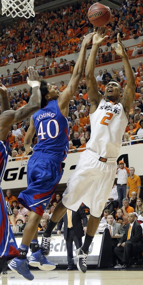 Photo - Oklahoma State 's Le'Bryan Nash (2) shoots over Kansas' Kevin Young (40) during the college basketball game between the Oklahoma State University Cowboys (OSU) and the University of Kanas Jayhawks (KU) at Gallagher-Iba Arena on Wednesday, Feb. 20, 2013, in Stillwater, Okla. Photo by Chris Landsberger, The Oklahoman