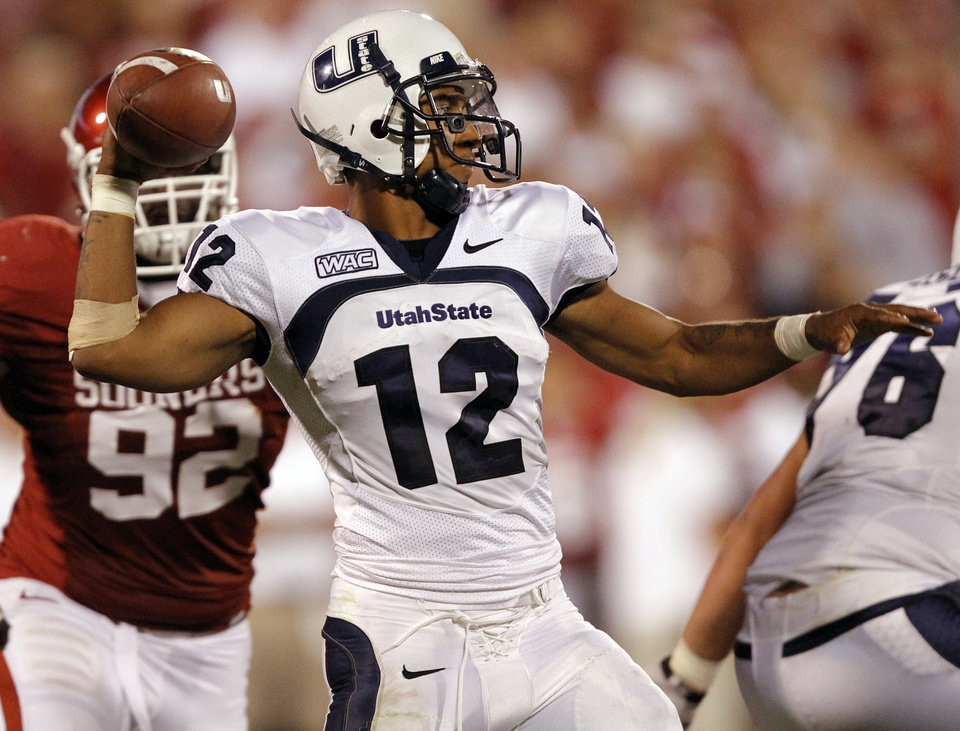 Photo - Utah State's Diondre Borel (12) looks to throw a pass during the second half of the college football game between the University of Oklahoma Sooners (OU) and Utah State University Aggies (USU) at the Gaylord Family-Oklahoma Memorial Stadium on Saturday, Sept. 4, 2010, in Norman, Okla.   Photo by Chris Landsberger, The Oklahoman