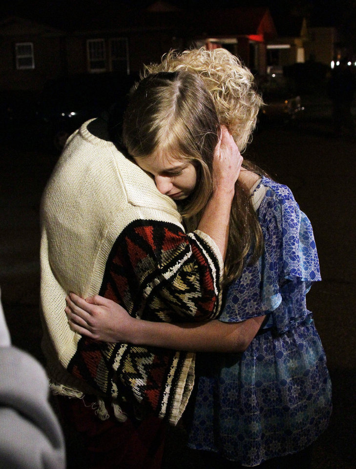 Photo -   Unidentified friends of the pilot of a small plane that authorities say crashed into a west Jackson, Miss., home shortly after 5 p.m. Tuesday evening, Nov. 13, 2012, hug each other as they await information as to the pilot and passengers. The home's resident is believed to have escaped but authorities have not released names of plane's passengers. (AP Photo/Rogelio V. Solis)