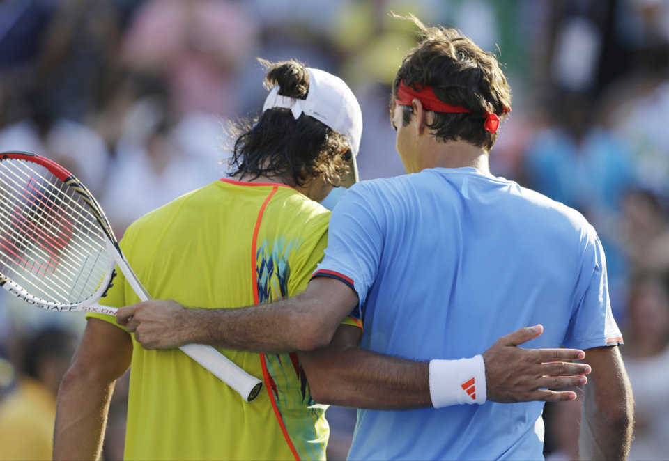 Photo -   Switzerland's Roger Federer and Spain's Fernando Verdasco leave the court after their match in the third round of play at the 2012 US Open tennis tournament, Saturday, Sept. 1, 2012, in New York. Federer won the match. (AP Photo/Mike Groll)