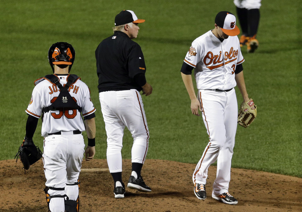 Photo - Baltimore Orioles manager Buck Showalter, center, watches as relief pitcher Brad Brach walks off the mound as he is relieved after giving up a solo home run to Washington Nationals' Jayson Werth in the seventh inning of an interleague baseball game, Wednesday, July 9, 2014, in Baltimore. (AP Photo/Patrick Semansky)