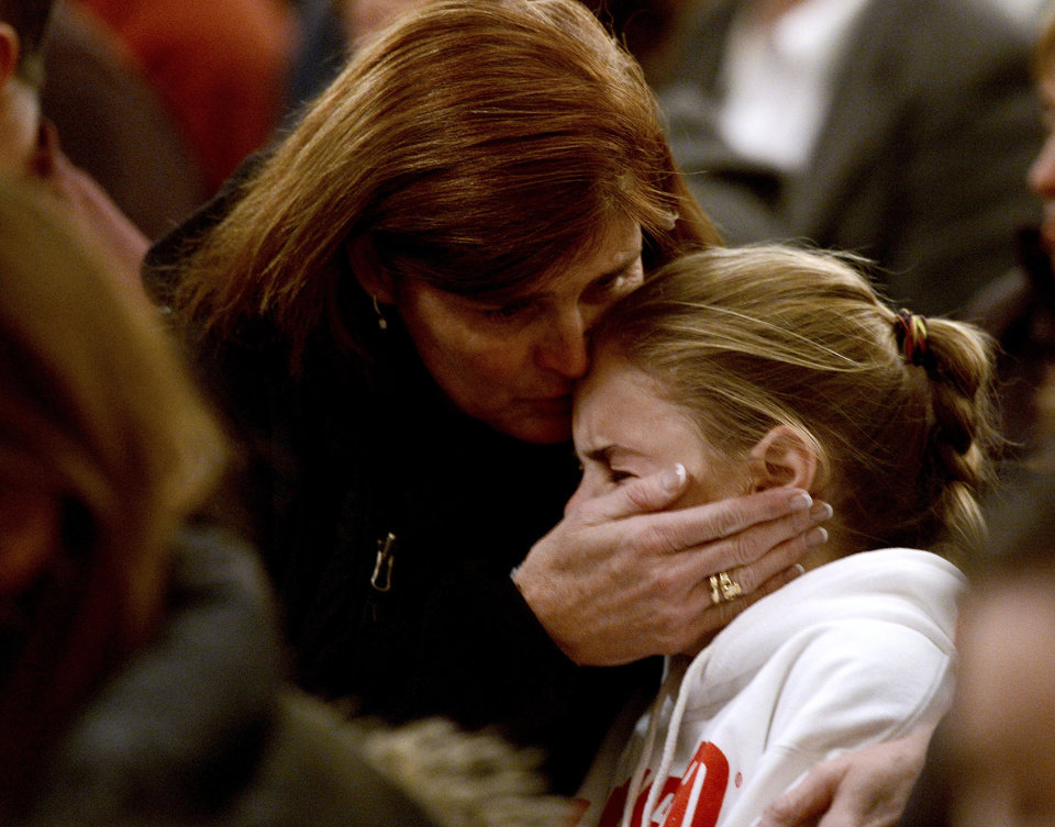 Photo - A woman comforts a young girl during a vigil service for victims of the Sandy Hook Elementary shooting, Friday, Dec. 14, 2012, at St. Rose of Lima Roman Catholic Church in Newtown, Conn. (AP Photo/Andrew Gombert, Pool)