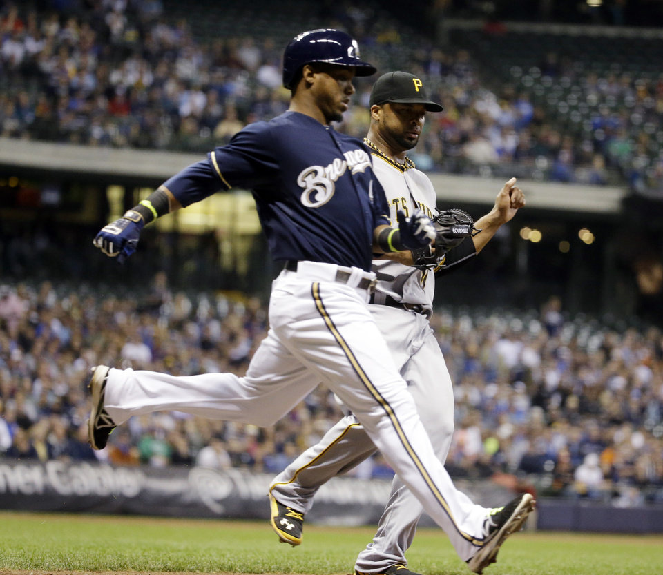 Photo - Milwaukee Brewers' Jean Segura beats Pittsburgh Pirates' Francisco Liriano to first during the fifth inning of a baseball game Wednesday, May 14, 2014, in Milwaukee. The play was ruled an error by first baseman Ike Davis. (AP Photo/Morry Gash)