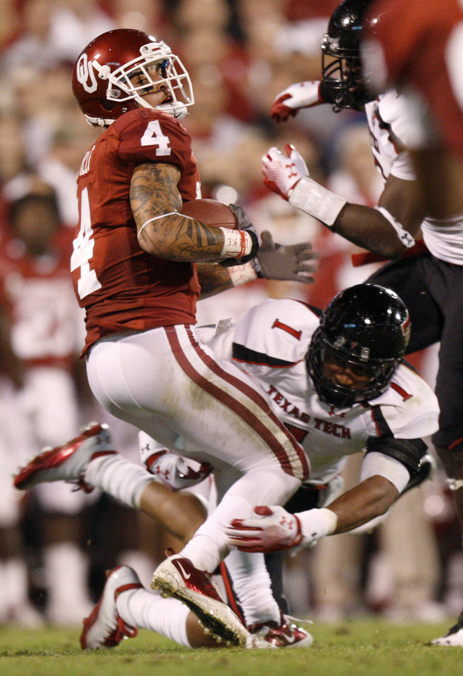Oklahoma's Kenny Stills (4) tries to get away from Terrance Bullitt (1) during the college football game between the University of Oklahoma Sooners (OU) and the Texas Tech University Red Raiders (TTU) at Gaylord Family-Oklahoma Memorial Stadium in Norman, Okla., Saturday, Oct. 22, 2011. Photo by Bryan Terry, The Oklahoman
