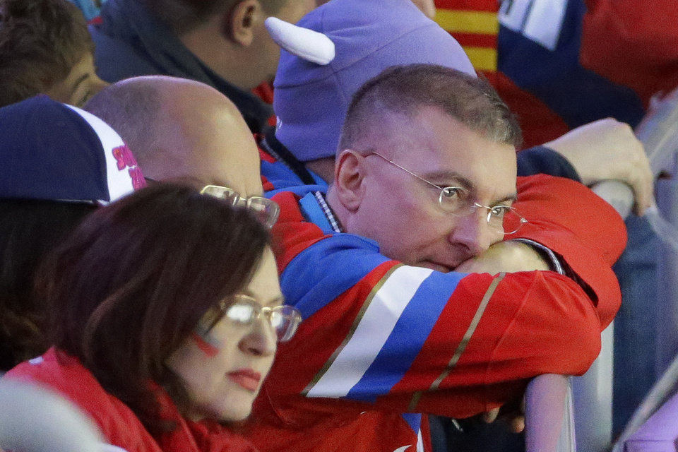 Photo - A Russian fan watches his team lose to Finland 3-1 during the third period of men's quarterfinal hockey game in Bolshoy Arena at the 2014 Winter Olympics, Wednesday, Feb. 19, 2014, in Sochi, Russia. (AP Photo/David J. Phillip )