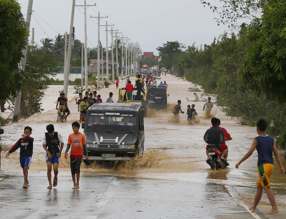 Photo - Residents wade through raging floodwaters brought about by Typhoon Koppu at Zaragosa township, Nueva Ecija province, north of Manila, Philippines Monday, Oct. 19, 2015. Slow-moving Typhoon Koppu blew ashore with fierce wind in the northeastern Philippines early Sunday, toppling trees and knocking out power and communications and forcing the evacuation of thousands of villagers.(AP Photo/Bullit Marquez)