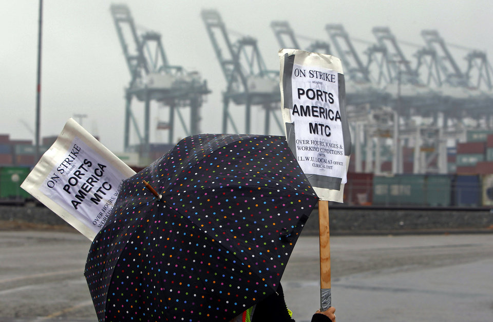 A clerical worker pickets in the rain at the Maersk cargo terminal, where container-handling cranes are in the up and idle position, background, at the Port of Los Angeles Thursday, Nov. 29, 2012. Cargo ships were stacking up at the ports of Los Angeles and Long Beach as a strike by about about 70 clerical workers shut down most of the terminals that together are the nation\'s busiest port complex. Dockworkers were refusing to cross the picket lines even though an arbitrator ruled the walkout invalid on Tuesday. By Thursday morning, at least 18 ships docked and inside the adjacent harbors were not being serviced, port spokesmen said. (AP Photo/Nick Ut)