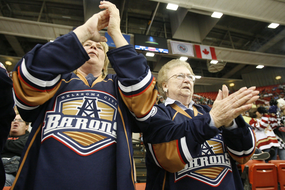 Photo - Chris Douglas, left, and Juanita Hess, of Oklahoma City cheer on the Barons after their first goal of franchise history during the AHL game between the Oklahoma City Barons and the Houston Aeros, Saturday, Oct. 9, 2010, at the Cox Convention Center in Oklahoma City. Photo by Sarah Phipps, The Oklahoman